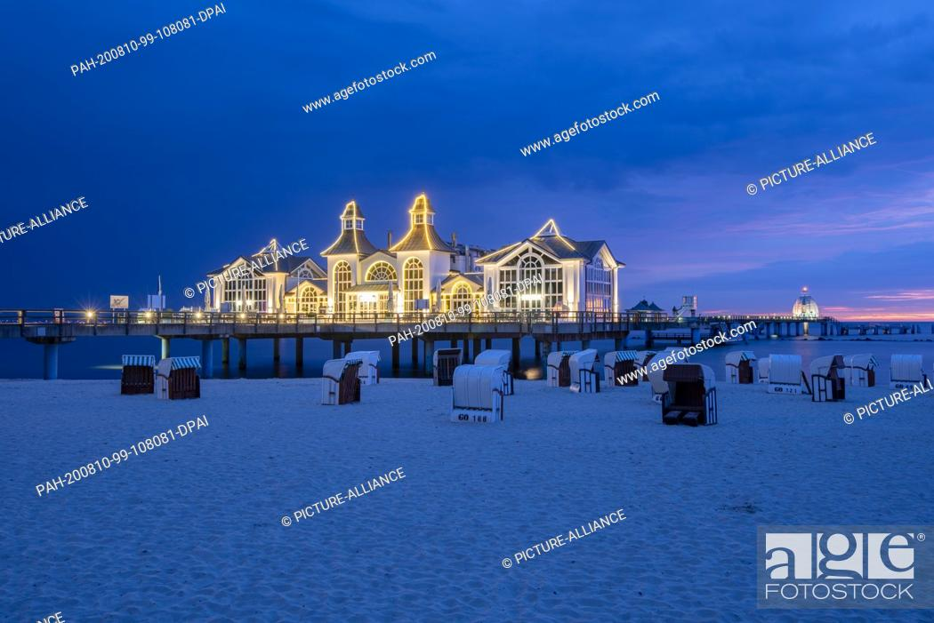 Stock Photo: 02 August 2020, Mecklenburg-Western Pomerania, Sellin: The pier with the famous diving gondola at the blue hour. The pier with restaurant was built in 1906.