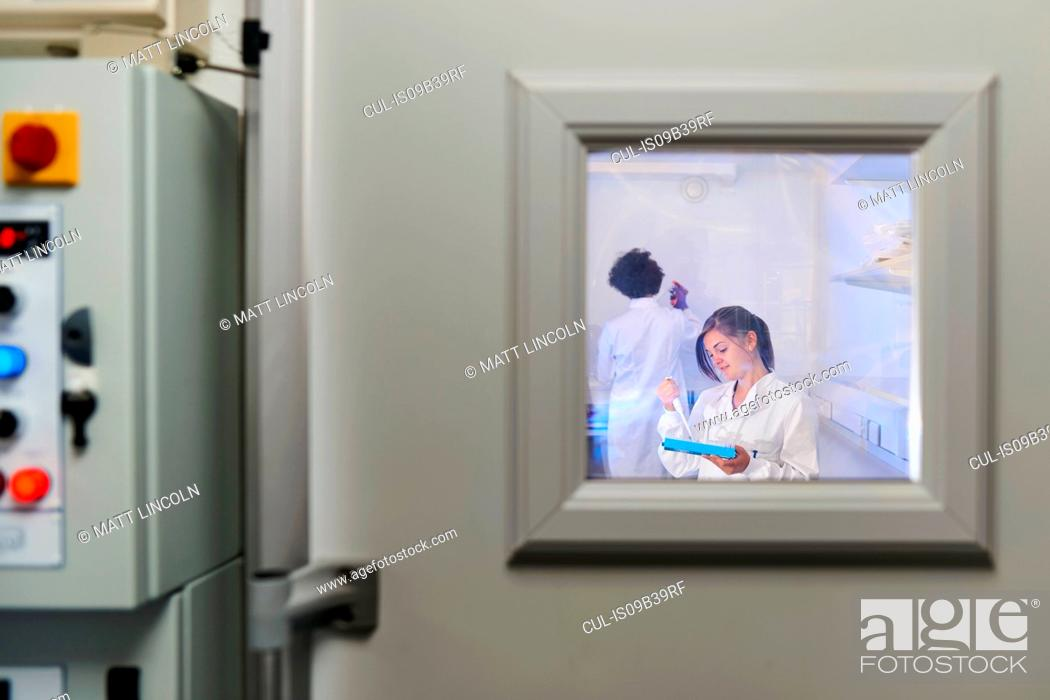 Stock Photo: View through window of scientists in laboratory.