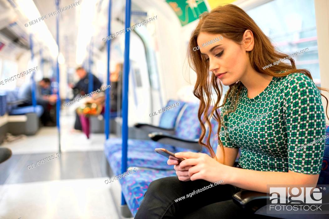 Stock Photo: Woman on train looking at smartphone.