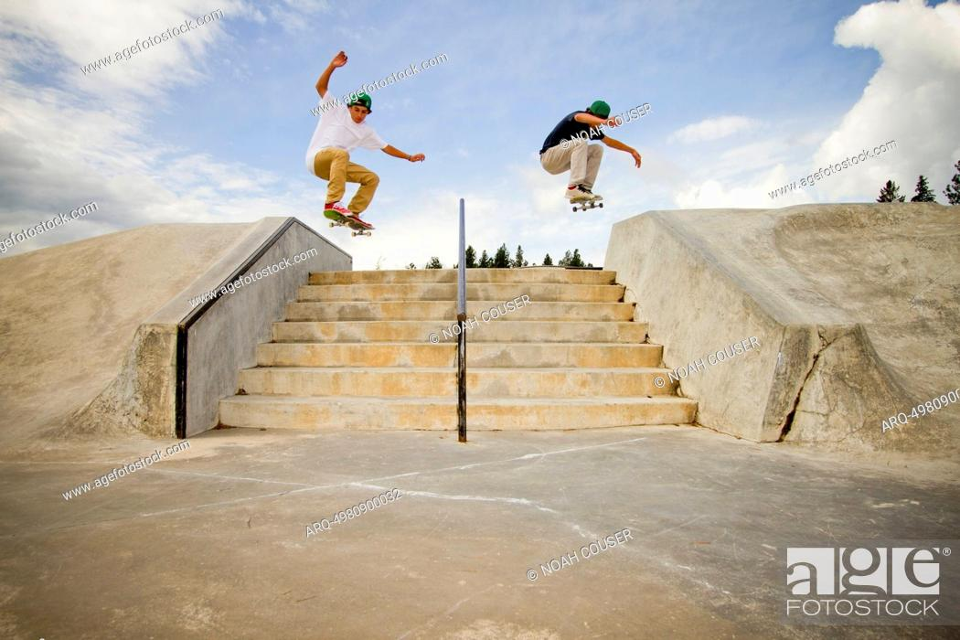 Stock Photo: Two skateboarders simultaneously clear a 7-stair gap at the skatepark in Whitefish, Montana.