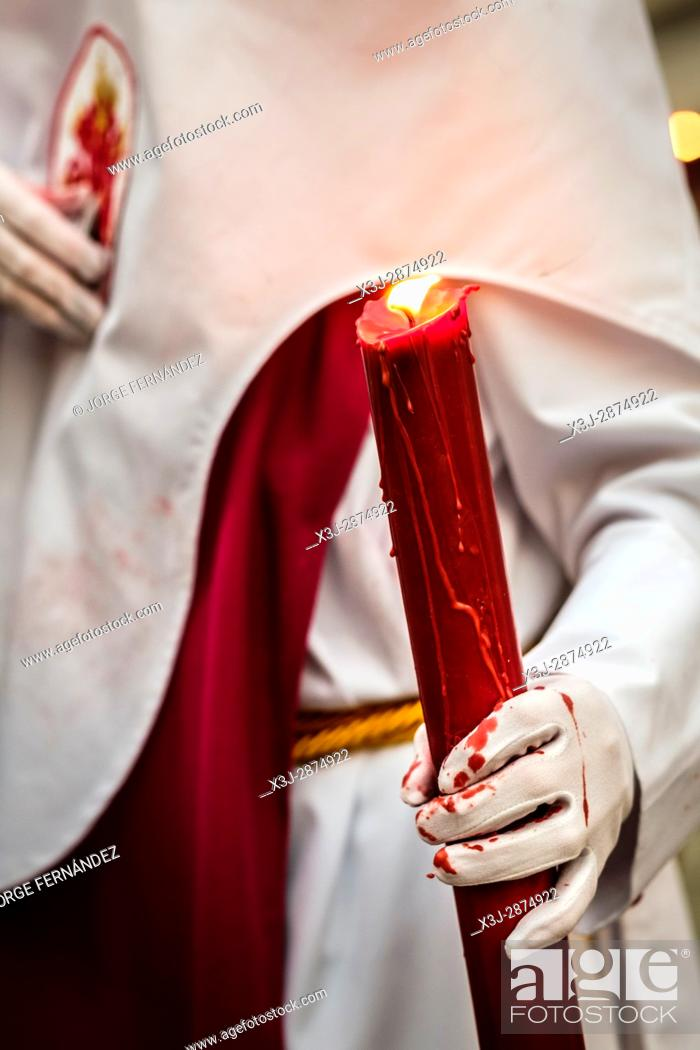 Stock Photo: Nazarenos participating in a religious procession, with the traditional robes and hoods and carrying candles during Semana Santa (Easter) in Seville.