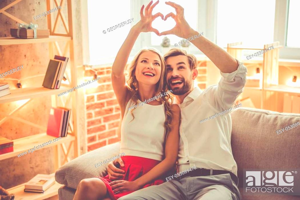 Stock Photo: Beautiful young couple is making heart of fingers and smiling while celebrating at home.