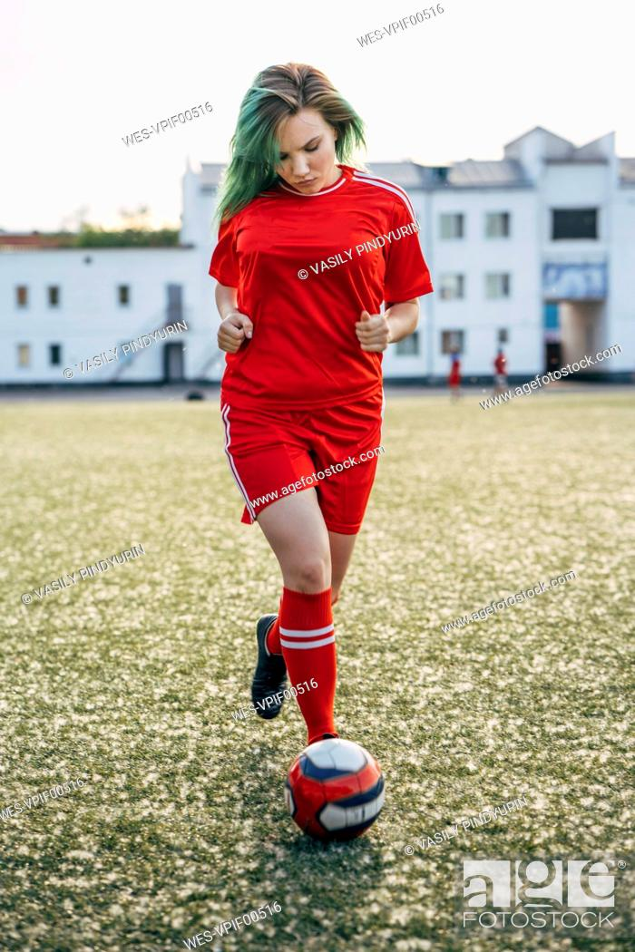 Photo de stock: Young woman playing football on football ground running with the ball.