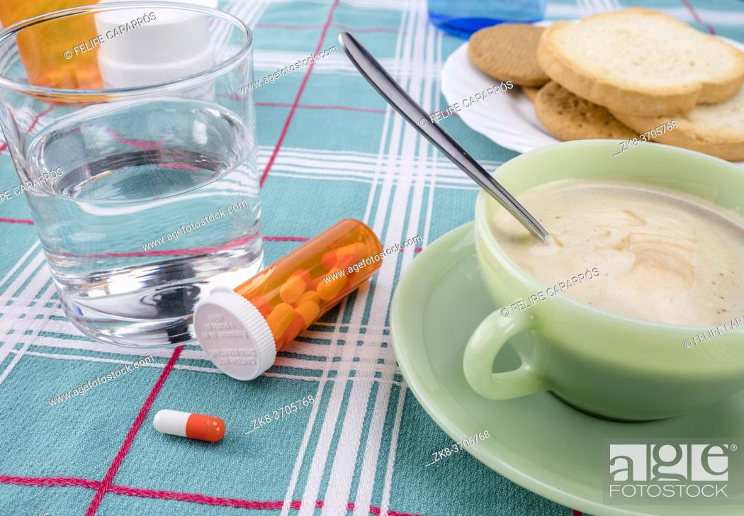 Photo de stock: Medication during breakfast, capsules next to a glass of water, conceptual image, horizontal composition.