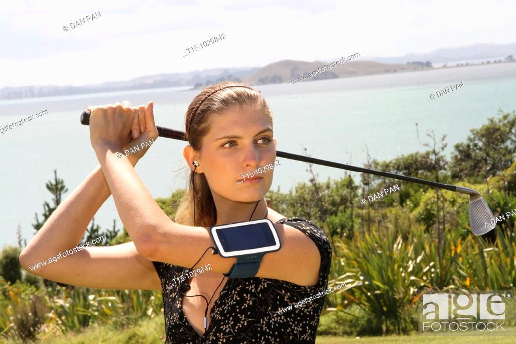 Stock Photo: woman golfing listening to music.