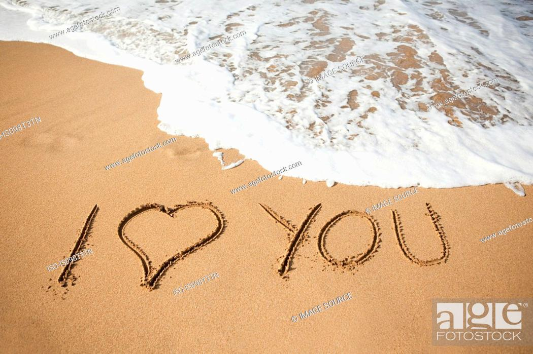 Stock Photo: I love you written in sand.