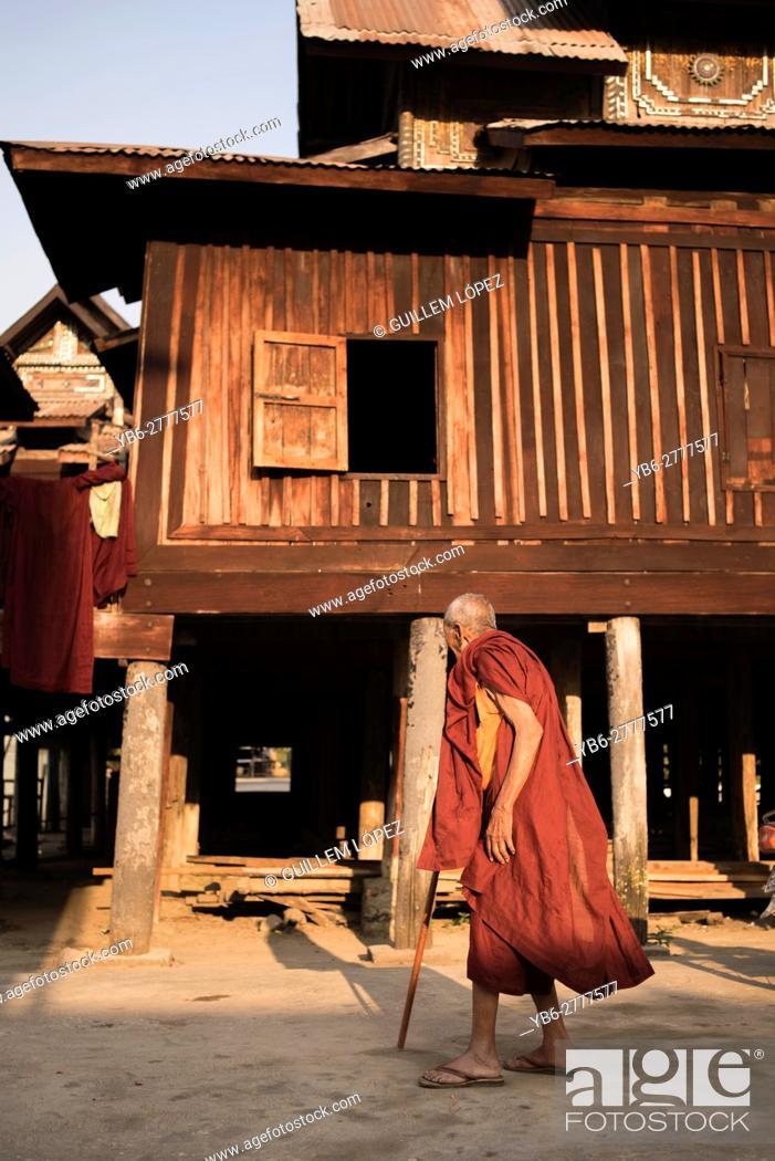 Stock Photo: Old Buddhist monk walking by the Shwe Yan Pyay Monastery in Nyaungshwe, Myanmar.