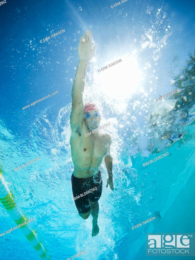 Stock Photo: Mixed race man swimming in swimming pool.