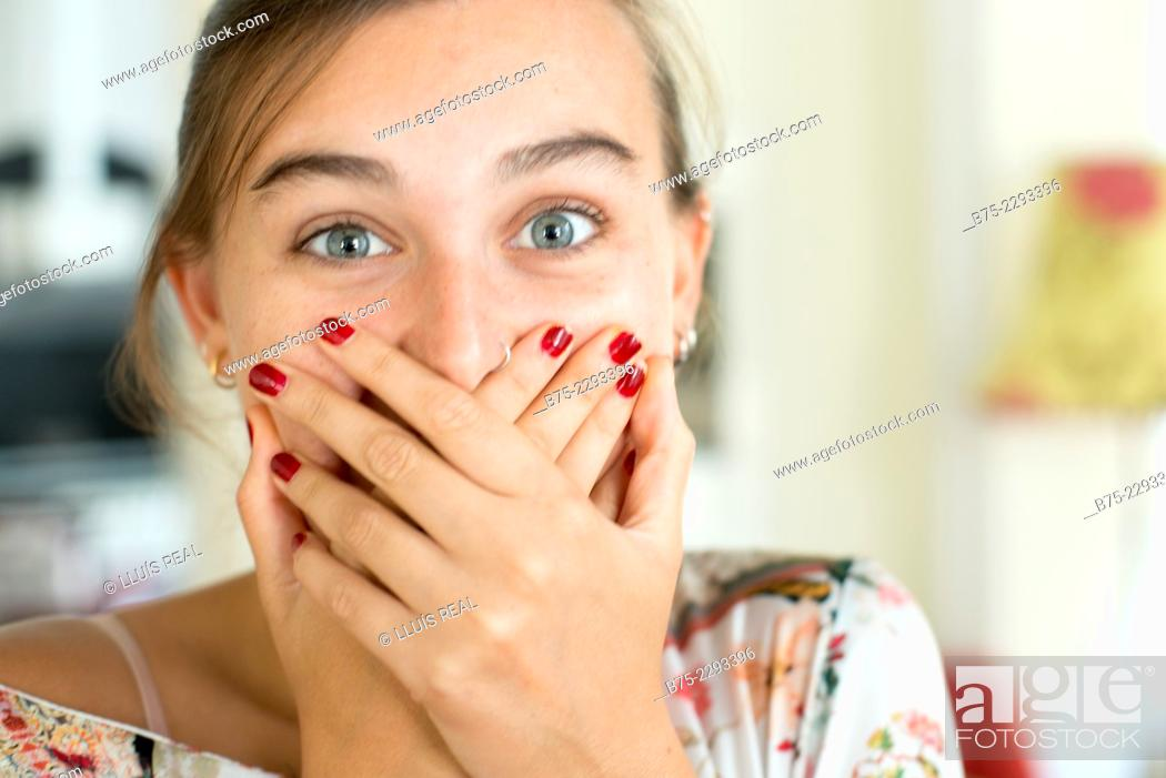 Stock Photo: Portrait of young girl with blue eyes and a nose piercing, looking at the camera with her hands covering her mouth with an expression of happy surprise.