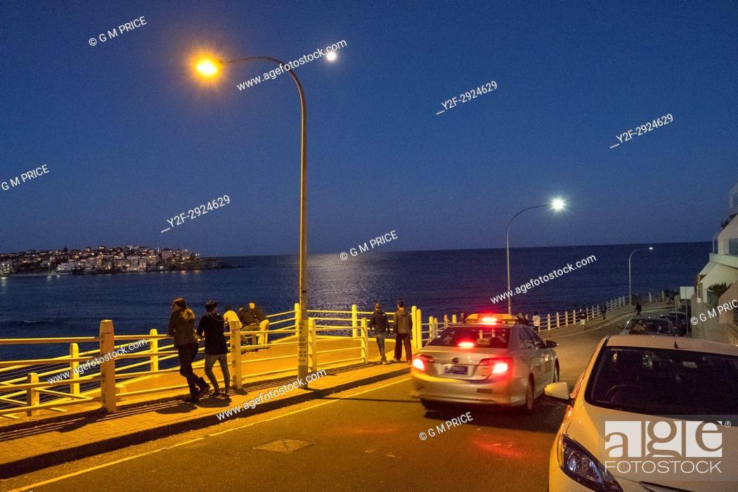 Imagen: people look over Bondi Beach on moonlit evening, Sydney.