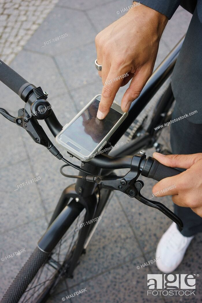 Stock Photo: Cropped image of businessman using mobile phone on bicycle handle while standing at street.