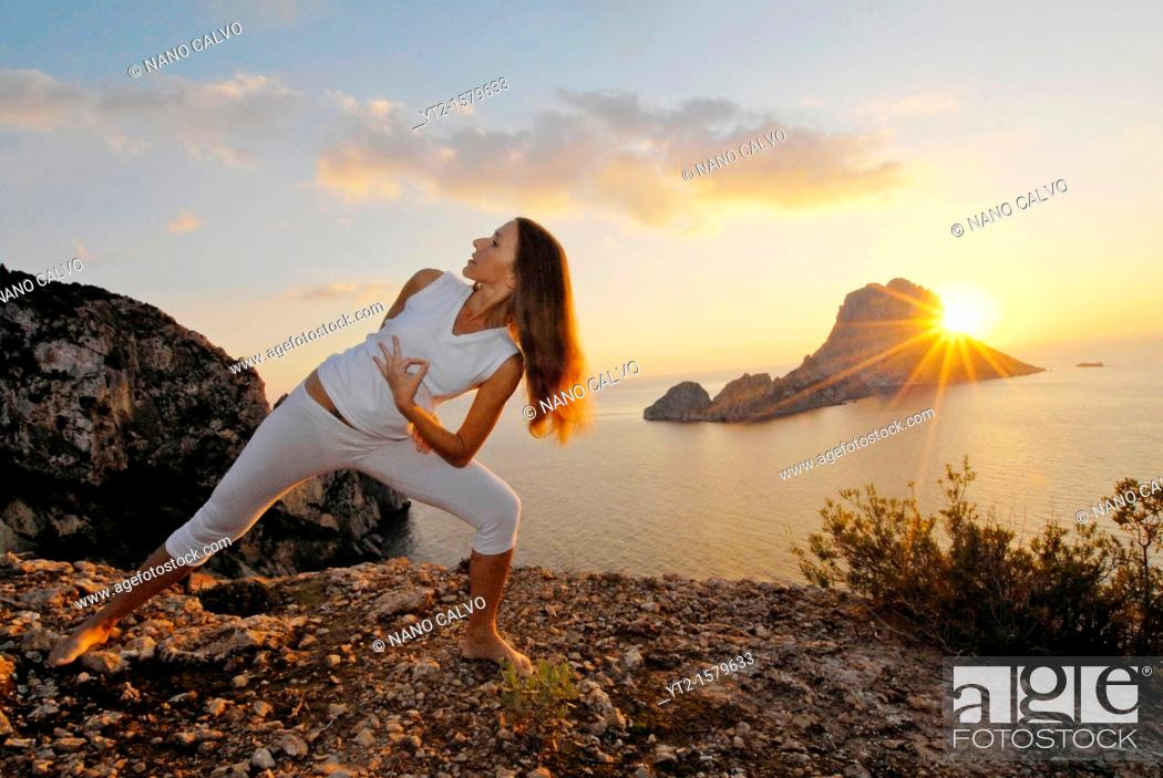 Stock Photo: Yoga Teacher Lena Tancredi, doing yoga at sunset in Ibiza, with Es Vedra in view.