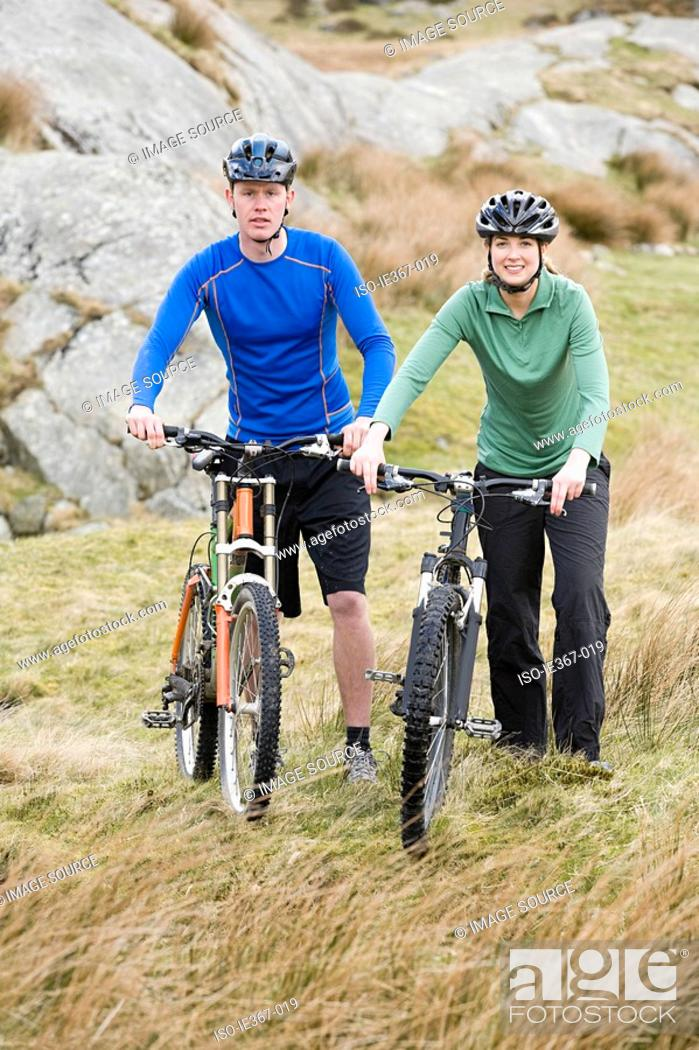Stock Photo: A couple pushing bikes up a hill.