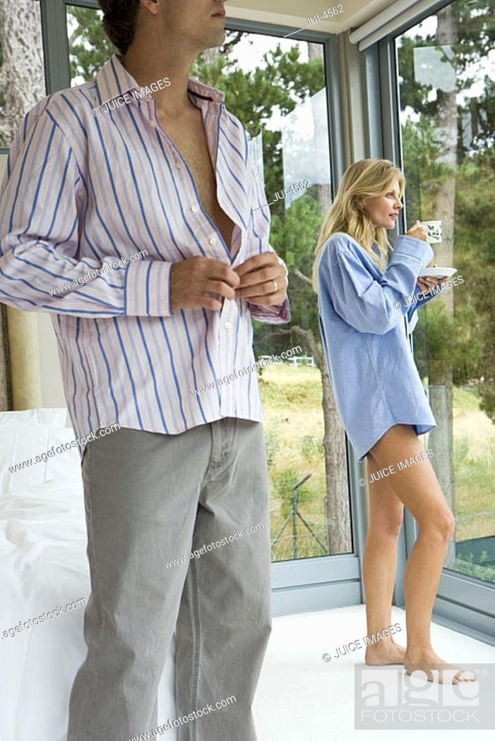 Stock Photo: Couple relaxing in bedroom, woman in man's shirt drinking cup of tea, man getting dressed.