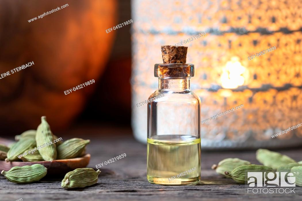 Stock Photo: A bottle of essential oil with whole cardamon seeds on a table.