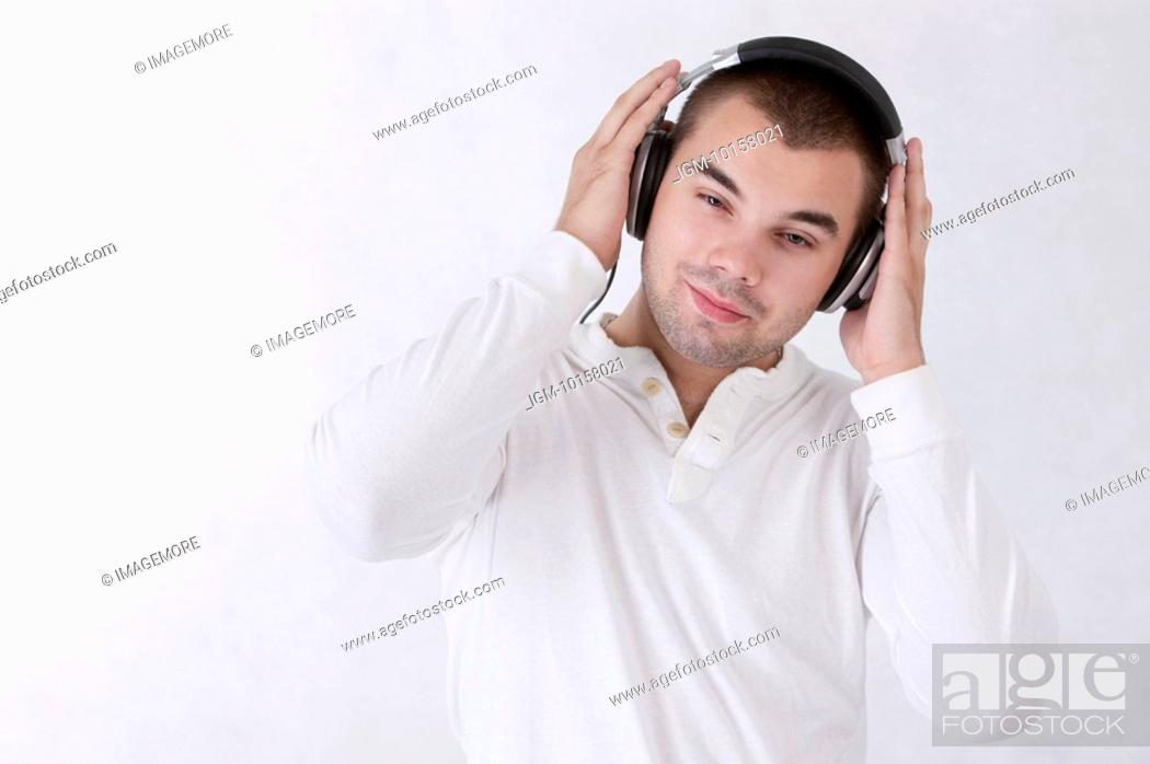Stock Photo: Young man listening music with headset and looking down with smile.
