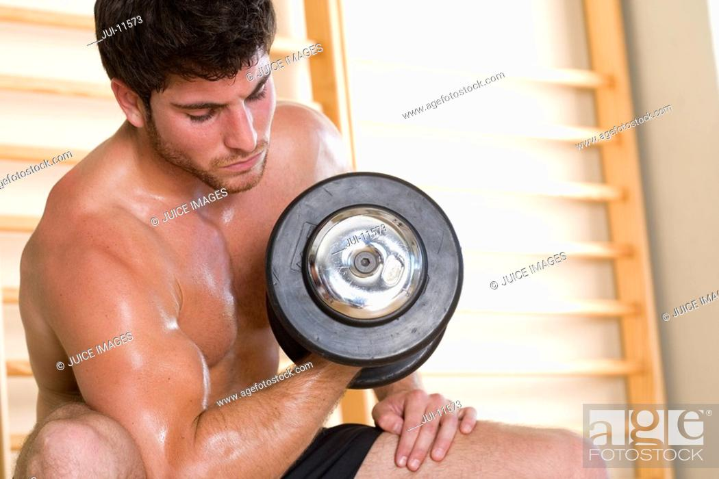 Stock Photo: Bare chested man lifting weights in gym, low angle view.