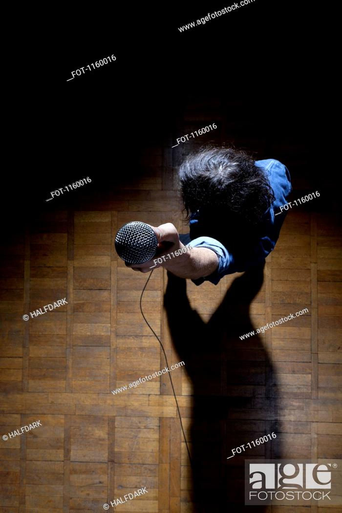 Stock Photo: High angle view of man holding mic up to camera.
