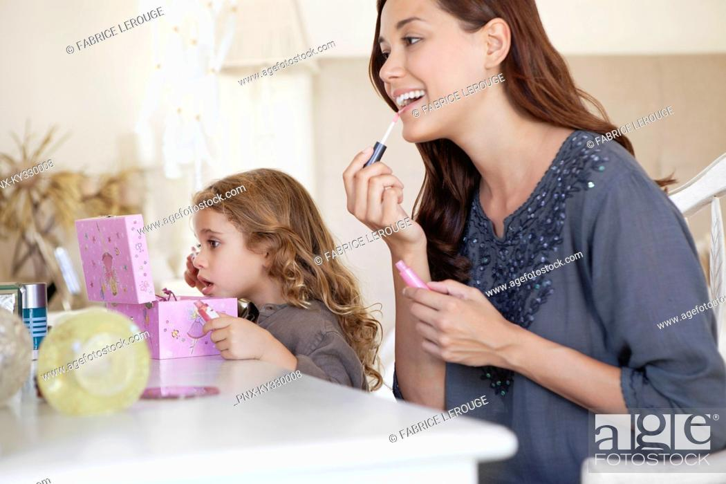 Stock Photo: Young woman and little girl applying make-up at dressing table.