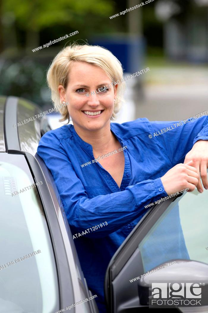 Stock Photo: Female car driver stands on opened door.