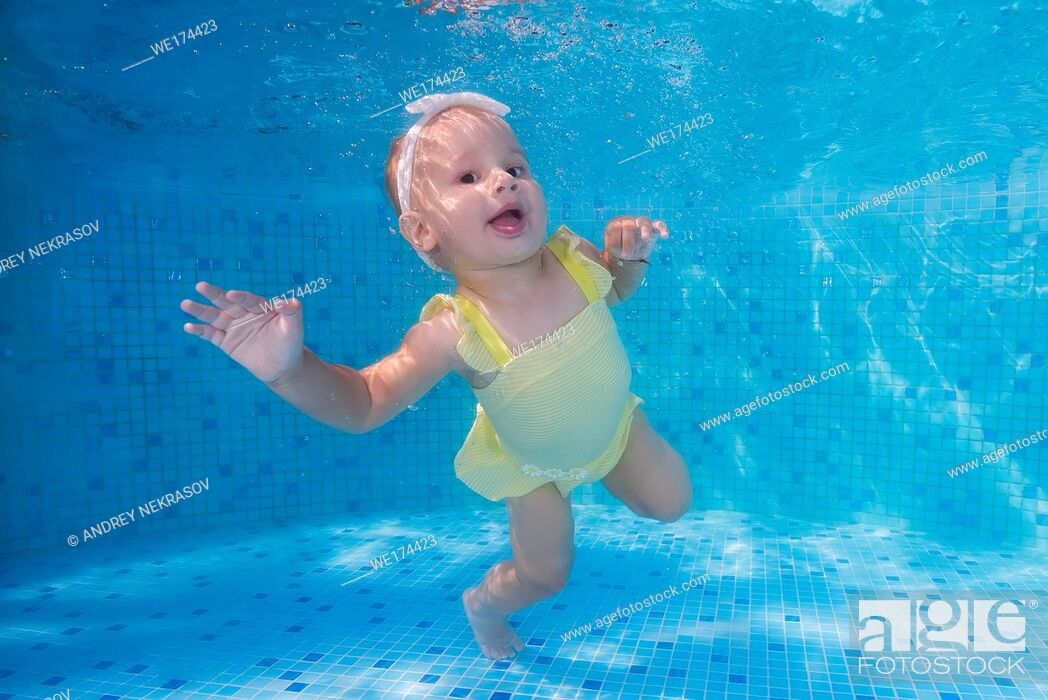 Stock Photo: Cheerful little girl in a yellow swimsuit underwater in the pool. Odessa, Ukraine.