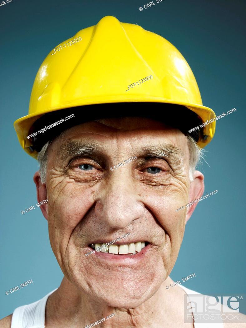 Stock Photo: Headshot of a senior man wearing a yellow hardhat.