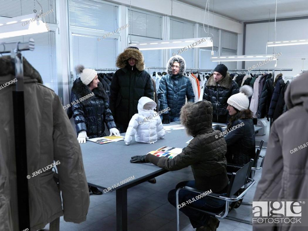 Stock Photo: Cloned product developers inspecting toddler's winter coat propped up on table in clothing manufacturer's sample studio digital enhancement.