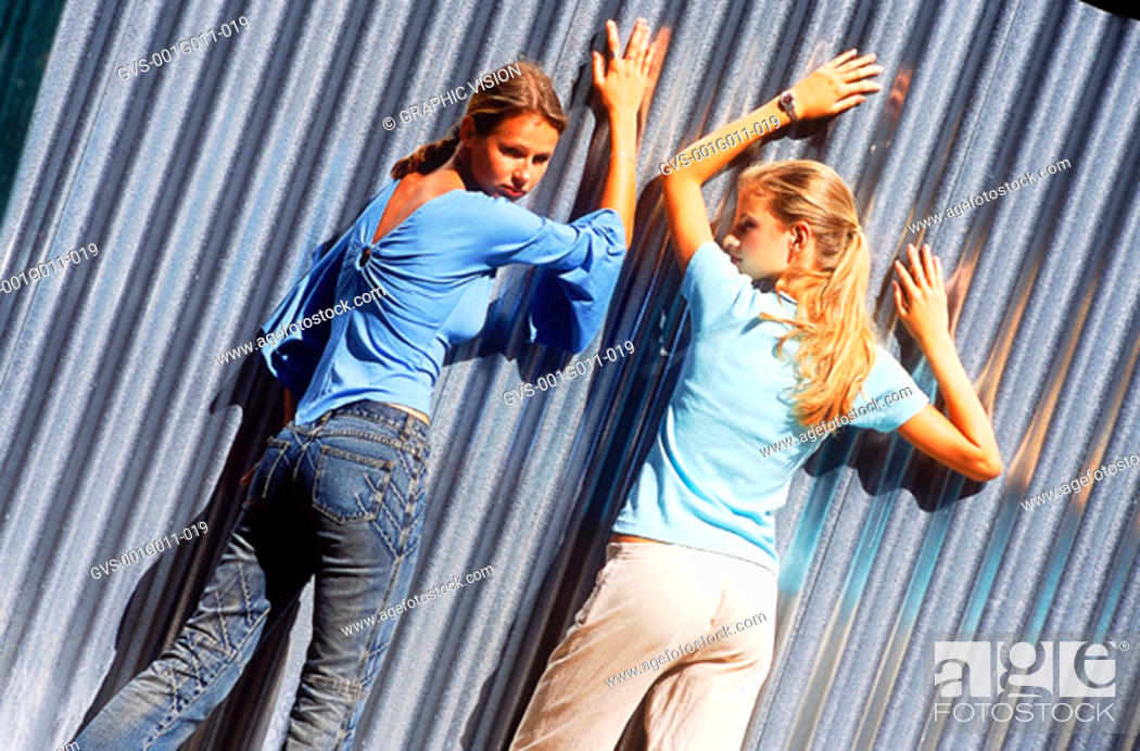 Stock Photo: Rear view of two young women leaning against a corrugated metal wall.