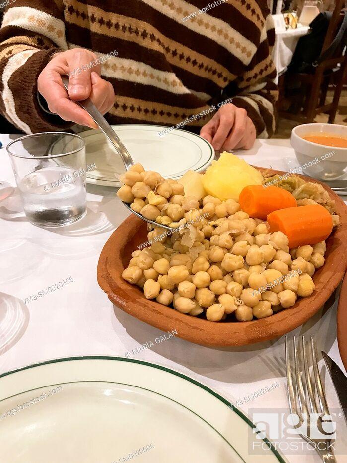 Imagen: Man serving cocido madrileño in a restaurant. Madrid, Spain.