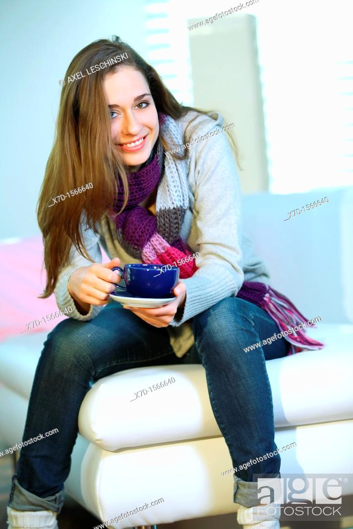 Stock Photo: woman relaxing on sofa drinking hot beverage.