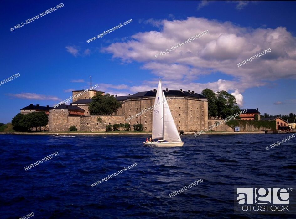 Stock Photo: A sailboat on the sea and castle in the background.