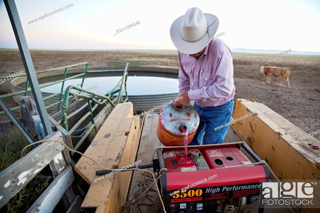 Yoder, Colorado - Dick Tanner fills a generator with red