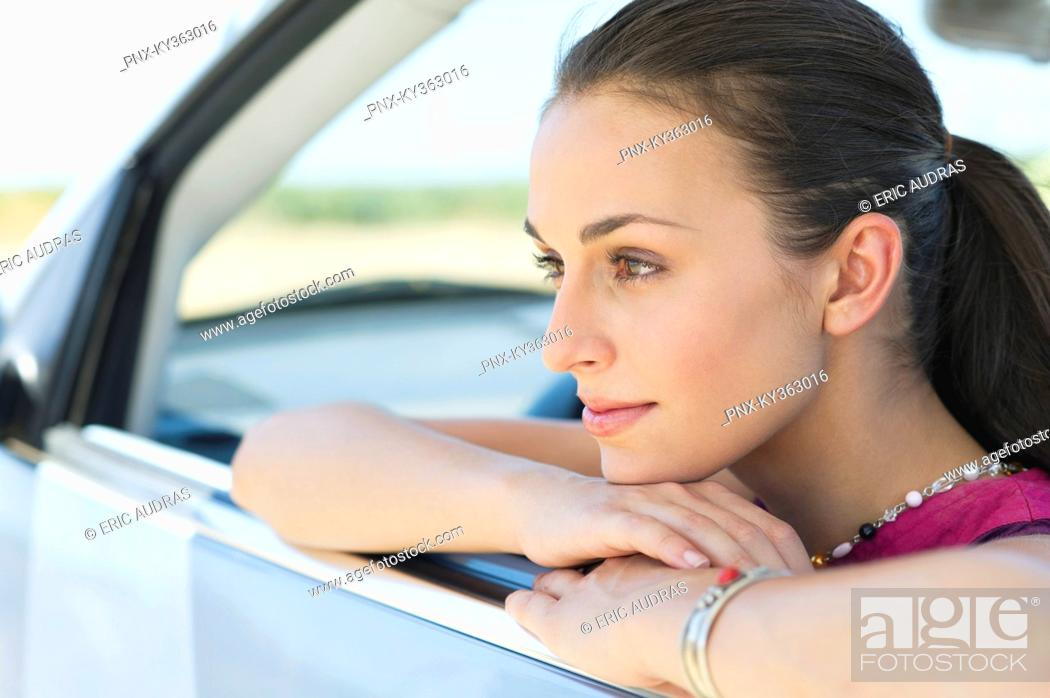 Stock Photo: Young woman looking out of car window.