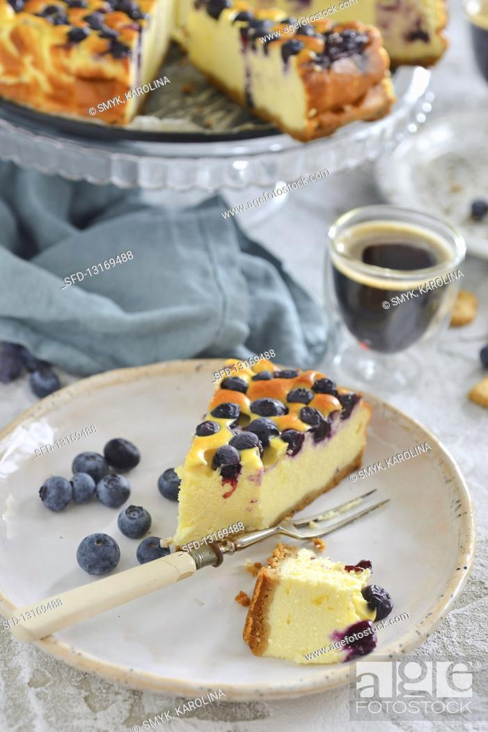 Stock Photo: A piece of cheesecake with blueberries on a plate.