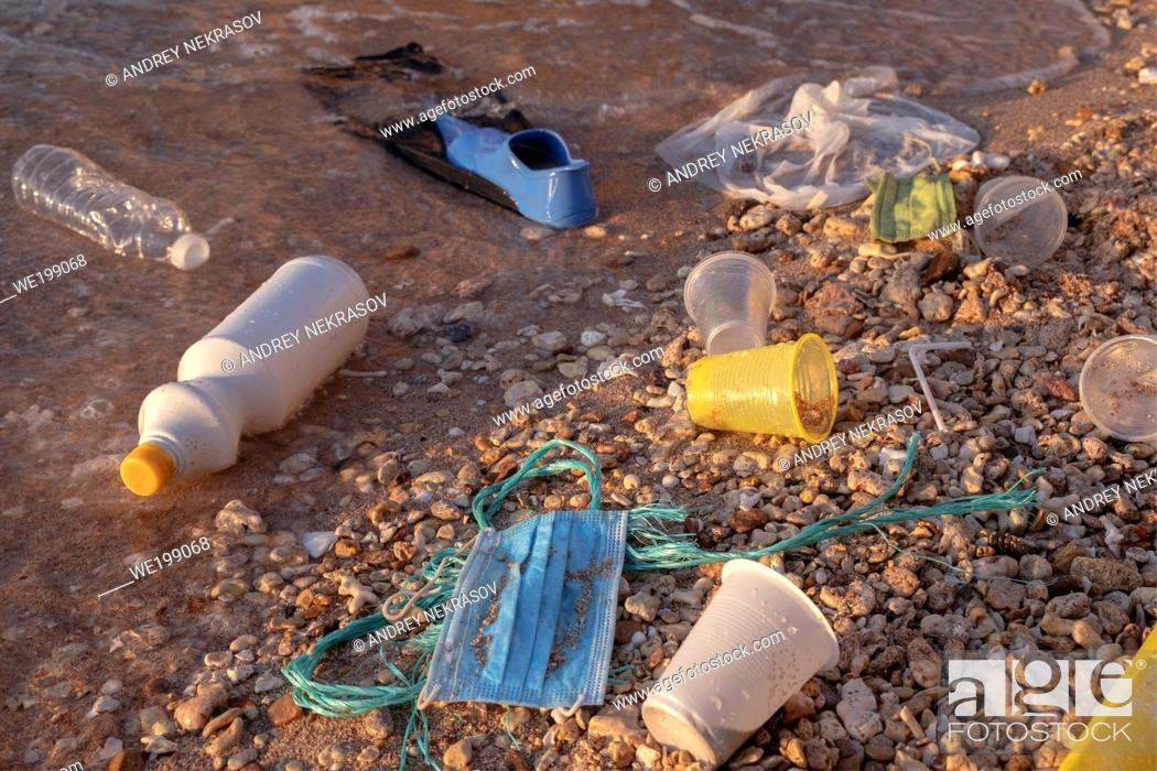 Stock Photo: RED SEA, SHARM EL SHEIKH, EGYPT - OCTOBER 18-26, 2020: Plastic debris and face masks on the beach in surf zone. Coronavirus COVID-19 is contributing to.