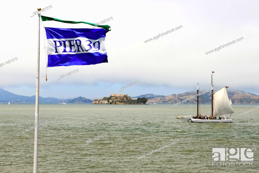 Imagen: Flag of pier 39 and a historic sailboat in the San Francisco Bay, Alcatraz Island at the back, San Francisco, California, USA, America.
