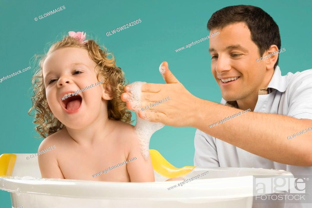 Stock Photo: Close-up of a mid adult man giving bath to his daughter.