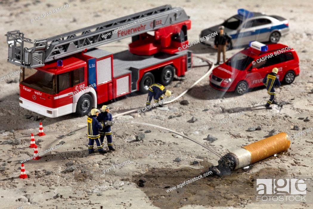 Stock Photo: Miniature figurines of firemen using a hose to put out a smoking cigarette butt.