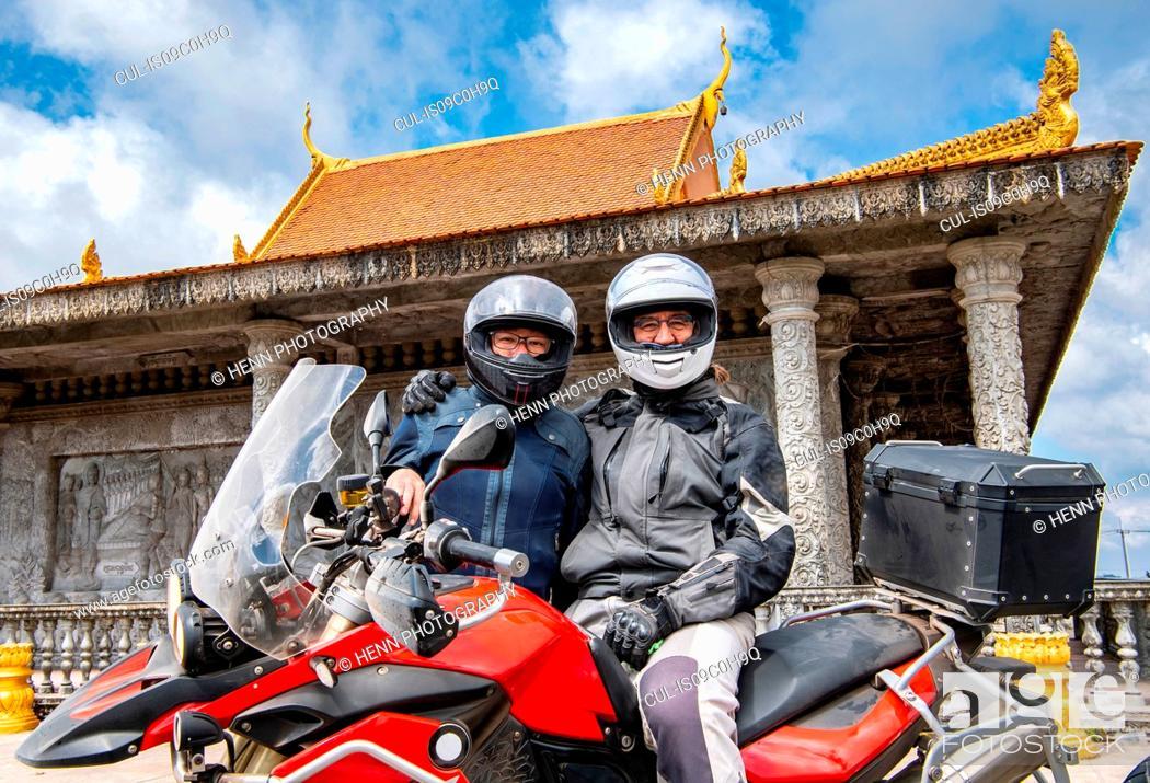 Stock Photo: Bikers posing on ADV motorbike in front of buddhist temple, Phnom Penh, Cambodia.