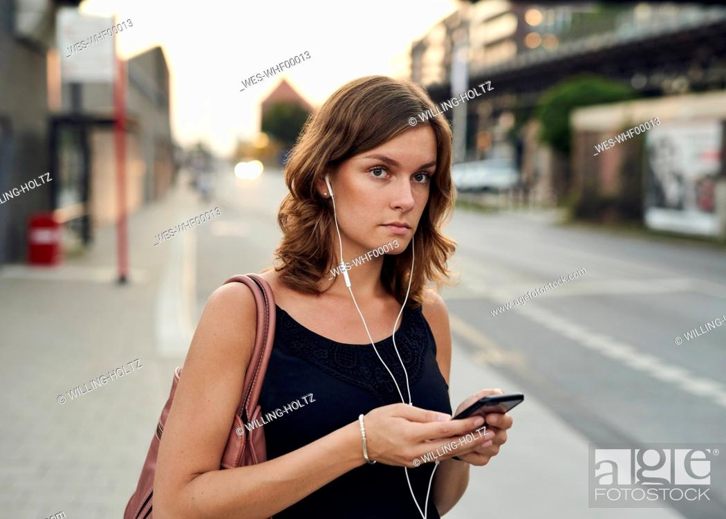 Stock Photo: Germany, Young woman with smart phone exploring Hamburg.