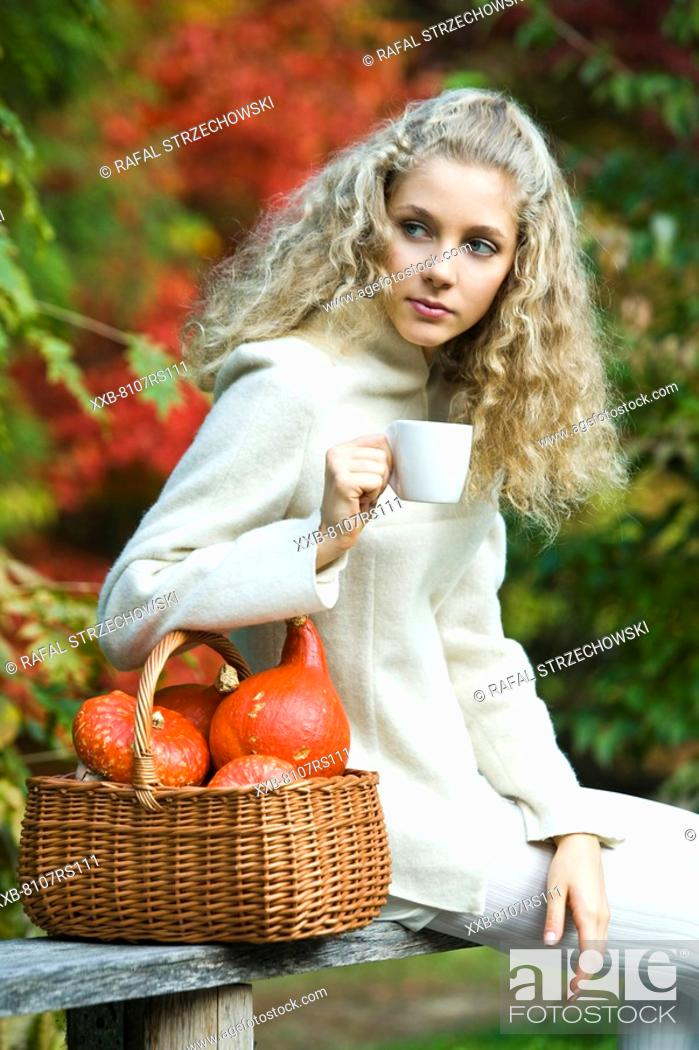Stock Photo: Young woman drinking tea in park.