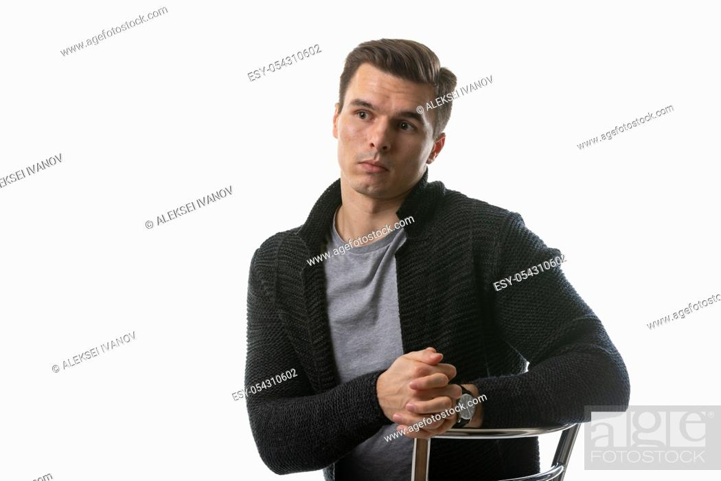 Stock Photo: The young guy thought hard, sitting on a chair.
