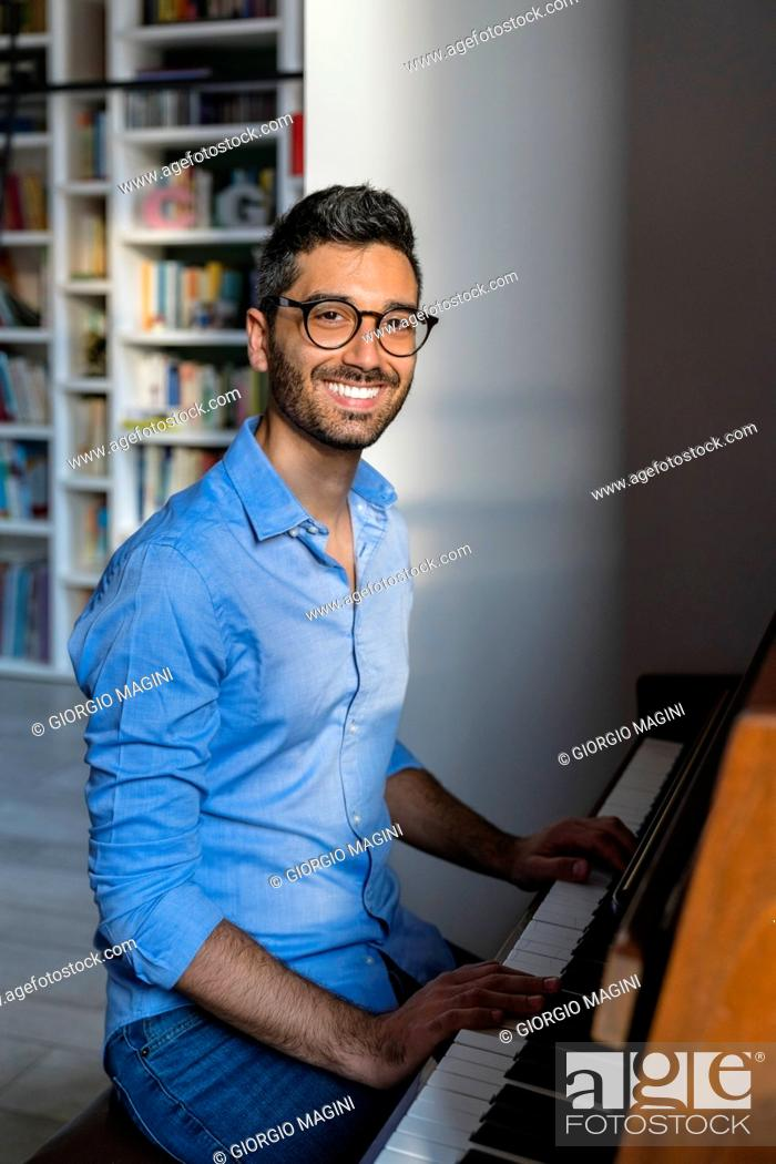 Imagen: Portrait of happy young man playing piano at home.