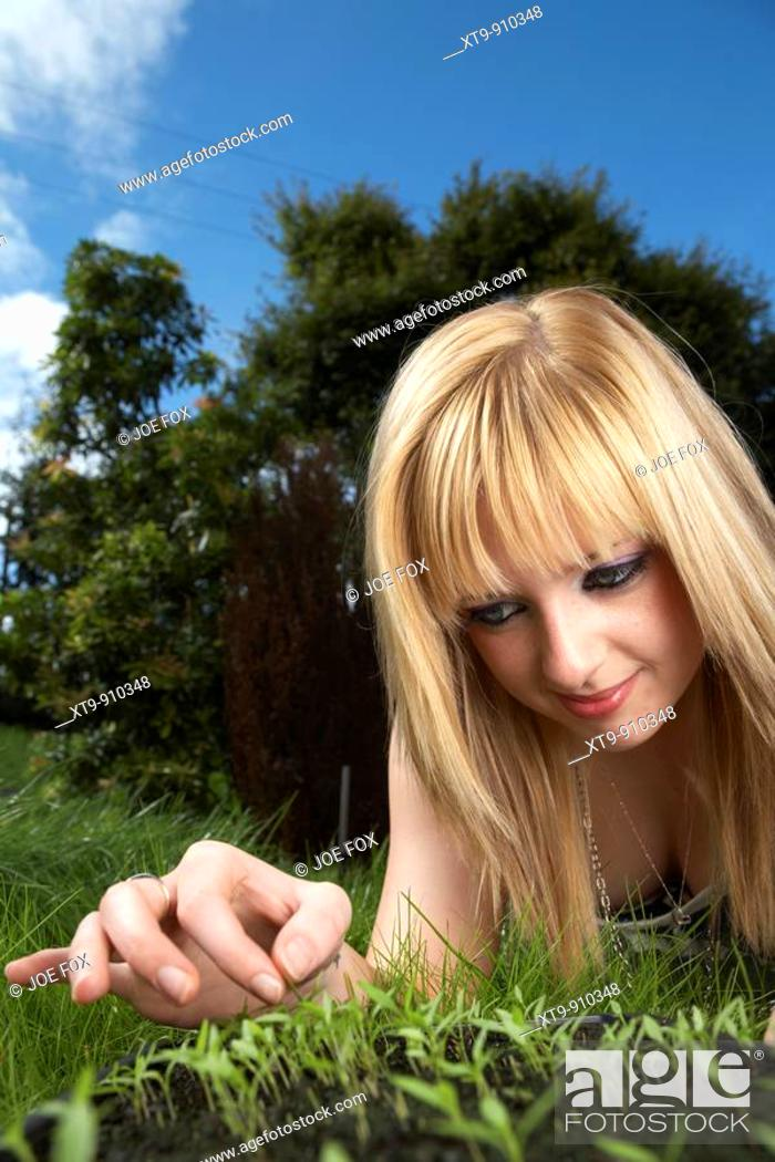 Stock Photo: young blonde haired woman late teens early twenties tending a tray of parsley herb seedlings in a garden.