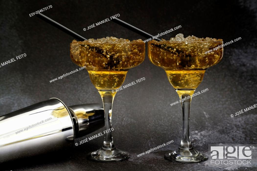 Stock Photo: Two iced tea cocktail glass with straw and cocktail shaker on dark background with copy space.