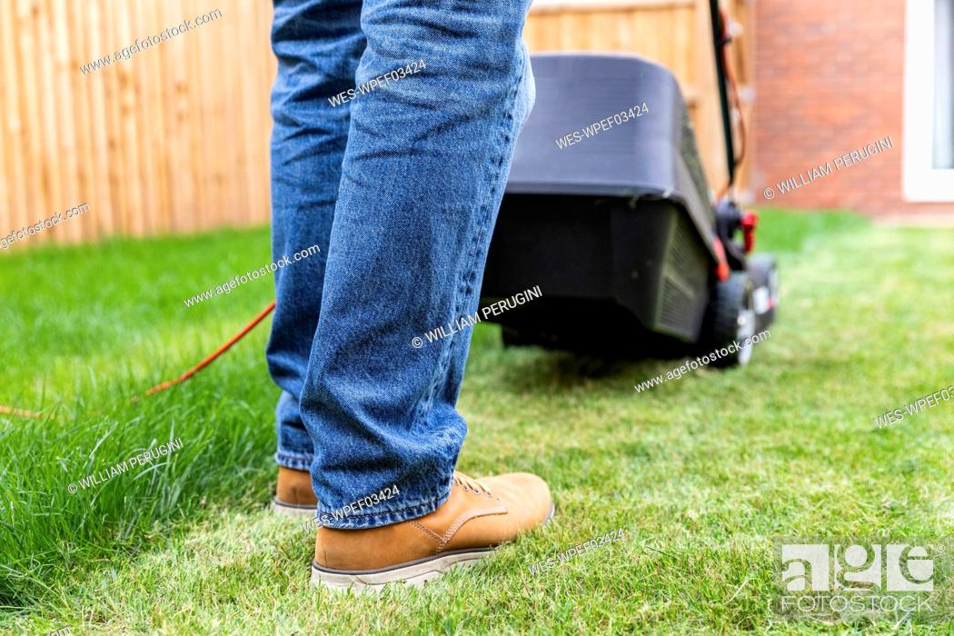 Stock Photo: Man standing with lawn mower at backyard.