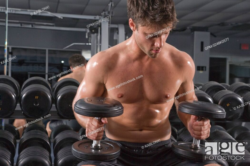 Imagen: Young man holding dumbbells in gym with mirror in background.