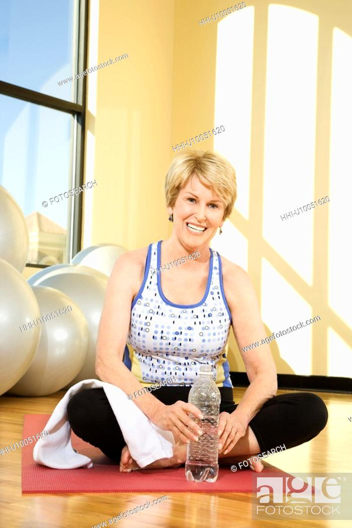 Stock Photo: Mature Caucasian female adult sitting on mat at gym.