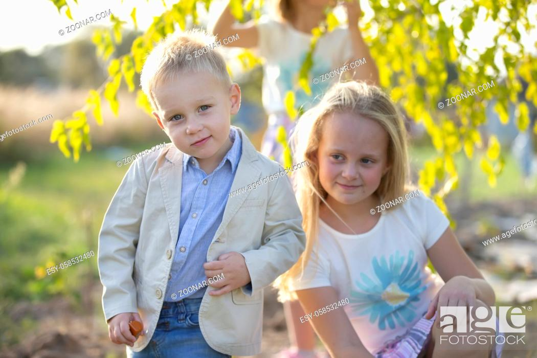 Photo de stock: Little boy in a suit on the background of his sister.