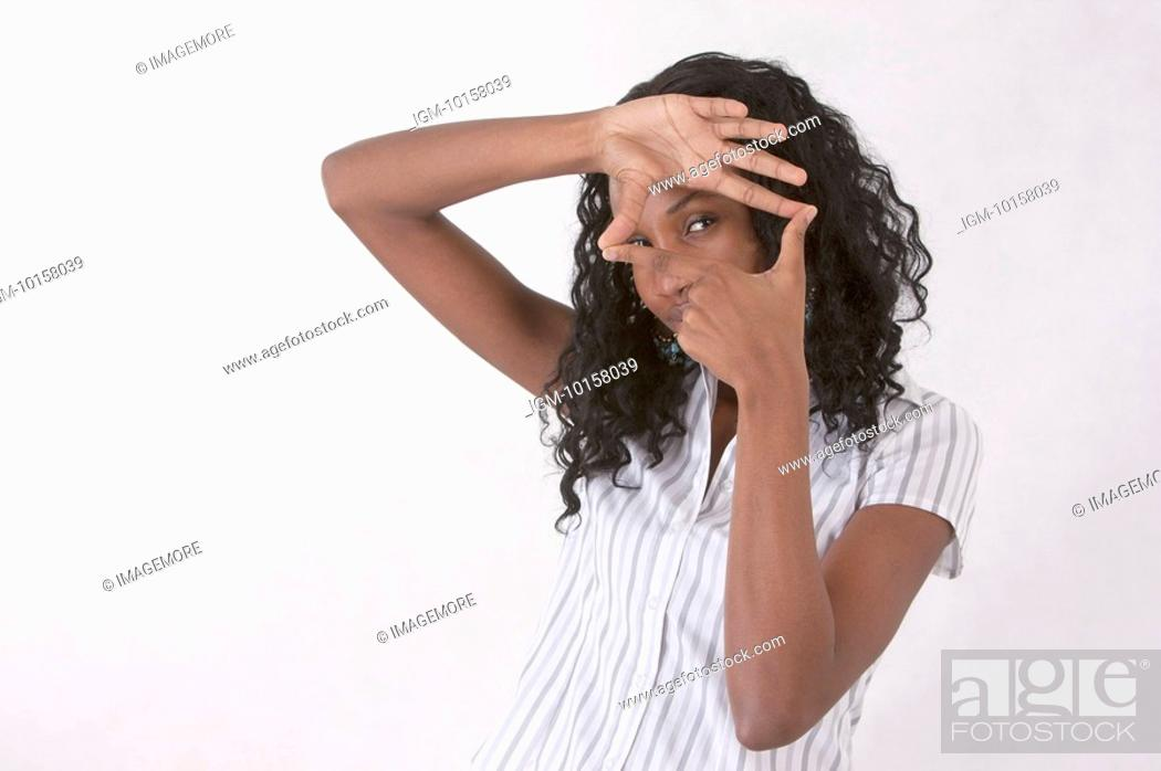 Stock Photo: Young woman making finger frame and looking at the camera.